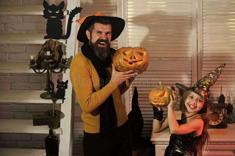 Father wizard and daughter witch with jack o lanterns royalty free stock photo
