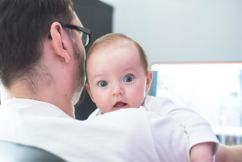 Father working from home with baby in his arms stock images