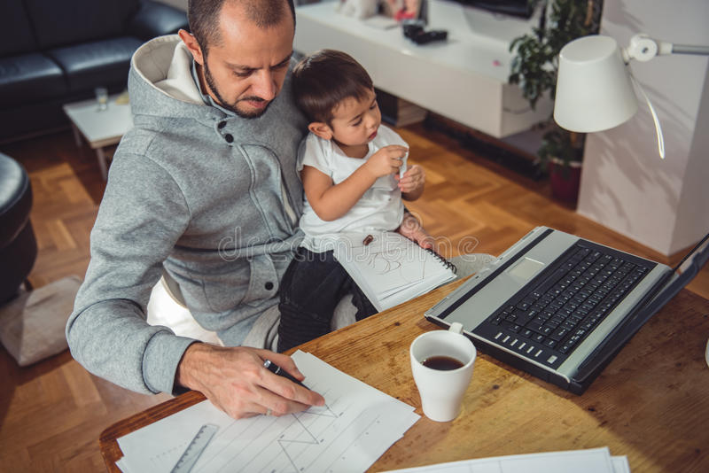 Father working at home and holding son on his lap stock photography