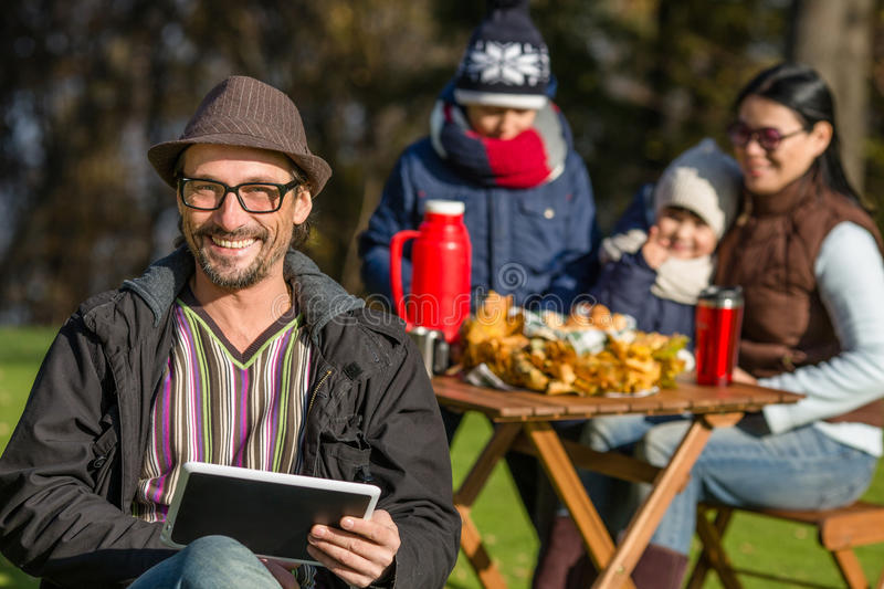 Father working on a picnic with his tablet PC stock images