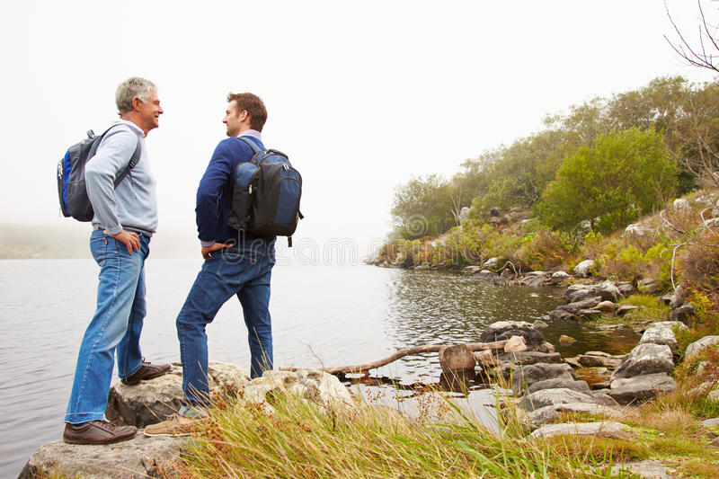 Father and young adult son standing by a lake stock image