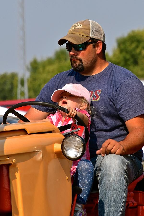 Father and young daughter drive tractor in a parade. ROLLAG, MINNESOTA, Sept 2, 2017: A father and young daughter drive a tractor in the parade held daily at the stock photo