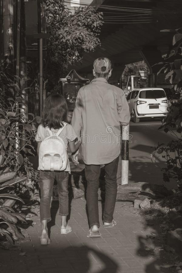 Father and young daughter walking together royalty free stock photography