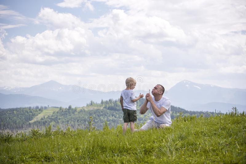 Father and young son are blowing dandelions sitting in the grass on a background of green forest, mountains and sky with clouds. stock photo
