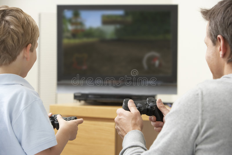 Father And Young Son Playing With Game Console Royalty Free Stock Images