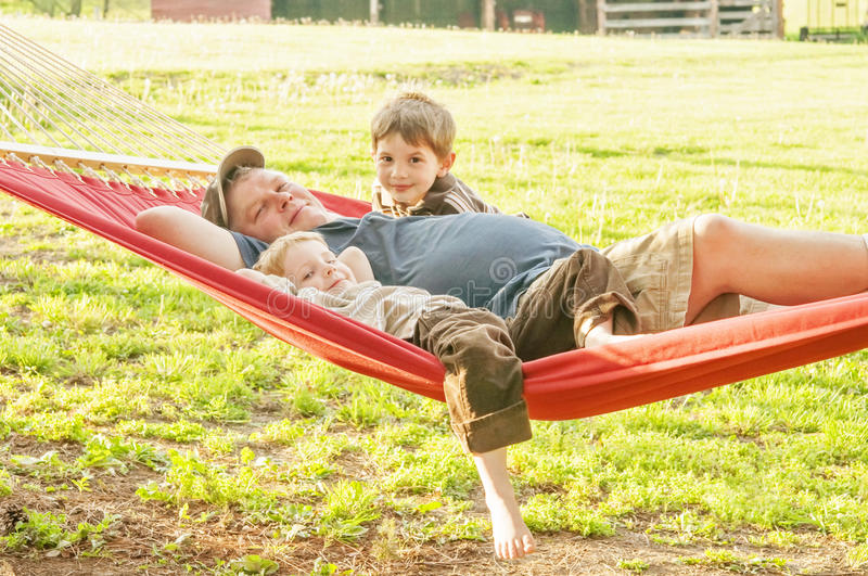 Father and young sons in hammock. Dad and kids relax in a red hammock in the country