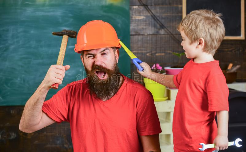 Fatherhood concept. Father, parent with beard in protective helmet teaching little son to use different tools in school. Workshop. Boy, child cheerful playing stock photo