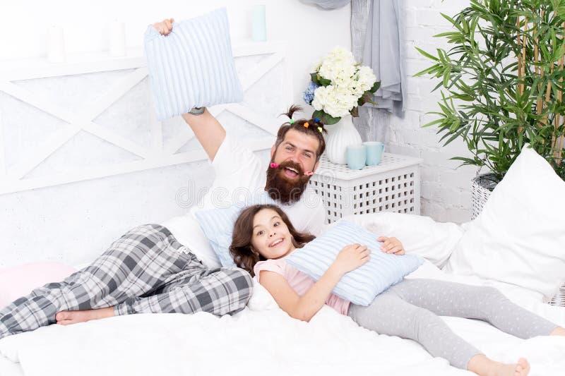 Fatherhood felice Pantaloni a vita bassa barbuti dell'uomo con le code di cavallo variopinte e la figlia dell'acconciatura pueril fotografia stock
