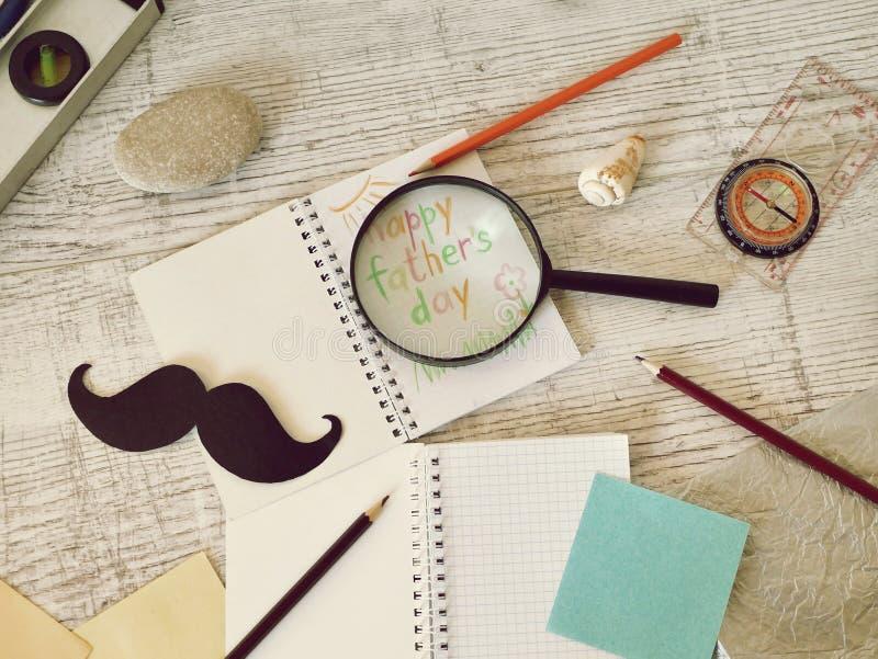 Инструменты отца, черный бумажный усик, лупа, карандаши и приветствуя надпись в тетради на светлом деревянном столе стоковая фотография