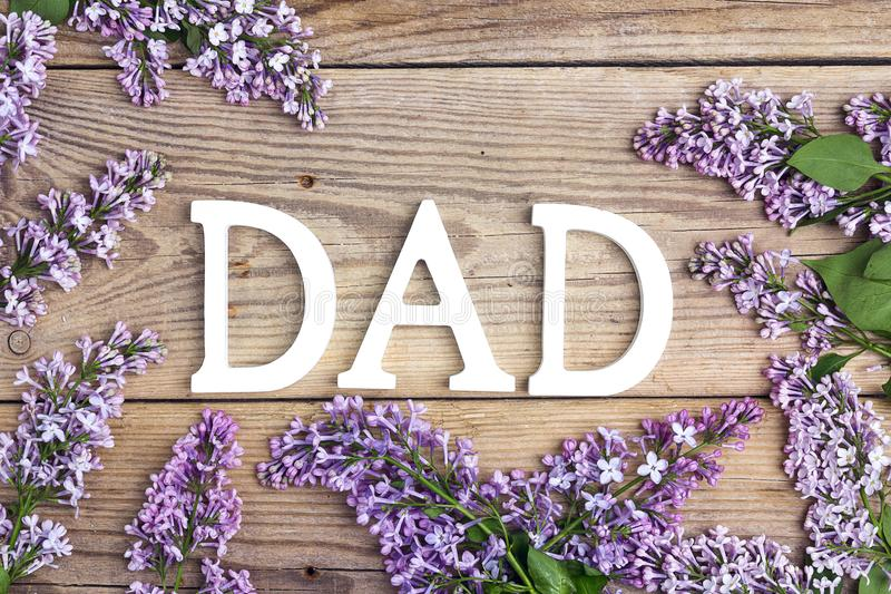 Fathers day background with letters and lilac flowers on old woo. Den table. Happy fathers day concept royalty free stock photo