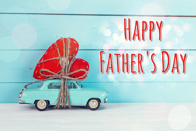 Fathers day background with miniature blue toy car carrying a he. Art on blue painted wooden planks. Happy fathers day concept royalty free stock images
