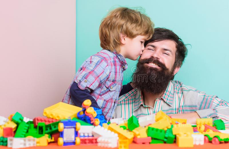 Fathers day. Bearded hipster and boy play together. Dad and child build of plastic blocks. Child care concept. Happy. Family. Child development and upbringing stock photo