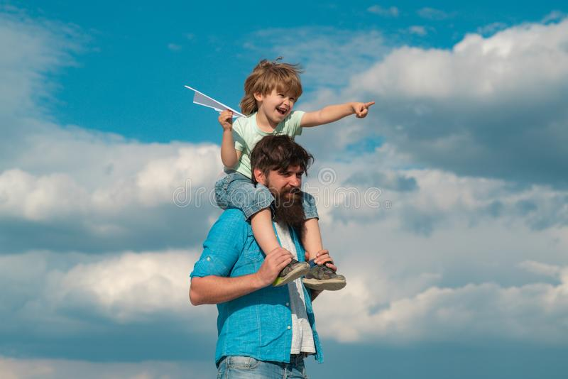 Fathers day. Carefree. Happy family father and child on meadow with a kite in the summer on the nature. Father and son. Building together a paper airplane royalty free stock photo