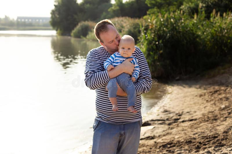 Fathers day. Dad kisses son. Happy family lifestyle. Family look for outdoor recreation. Sunny day on the river royalty free stock photography