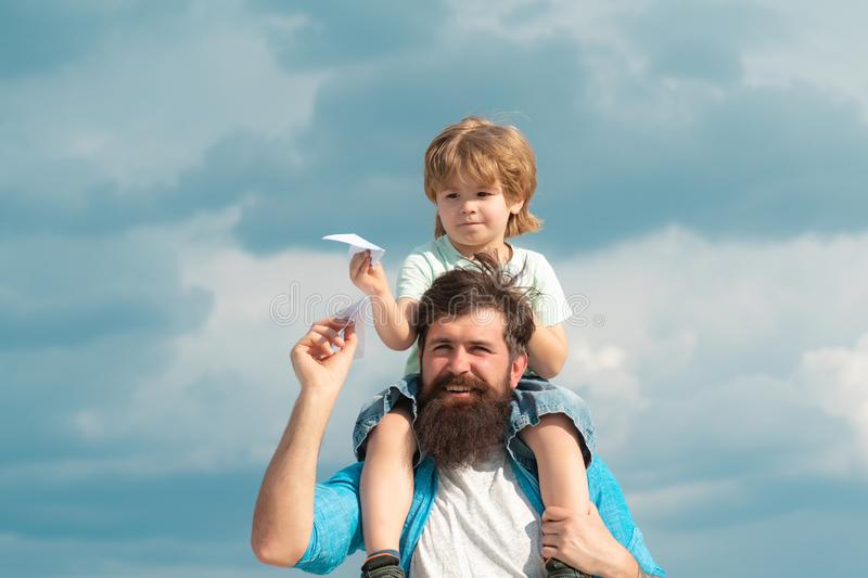 Fathers day. Family Time. Parenting. Happy father giving son back ride on sky in summer. Happy child playing with toy. Paper plane against summer sky background stock photos