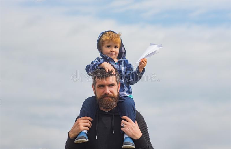 Fathers day. Father and son in the park. Cute boy with dad playing outdoor. Child sits on the shoulders of his father. Father giving son ride on back in park stock photography