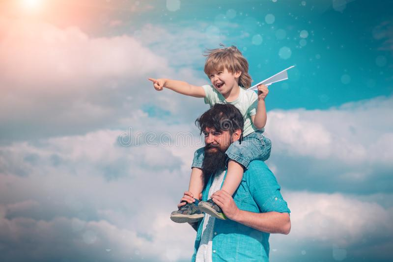Fathers day. Happy family father and child on meadow with a kite in the summer on the nature. Father and son building. Together a paper airplane royalty free stock photo