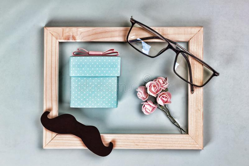Fathers day. Homemade gift box, the symbols of Father`s Day-glasses, mustaches, roses. CONCEPT congratulation AND GIFTS. Composit. Ion in a frame.top view stock images