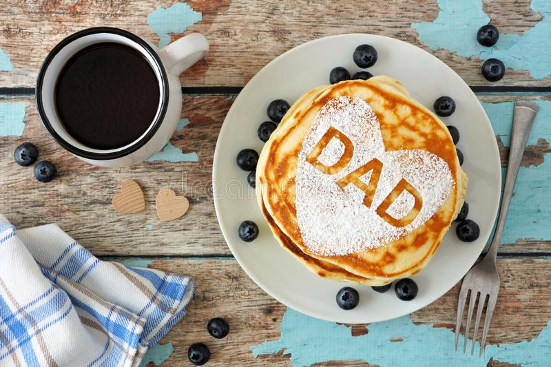 Fathers Day pancake breakfast with heart shape and DAD letters, top view on rustic blue wood. Fathers Day pancakes with heart shape and DAD letters. Fathers Day stock image