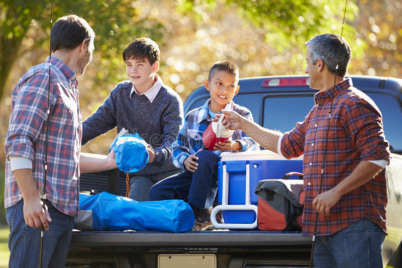 Fathers With Sons Unpacking Truck On Camping Holiday royalty free stock image