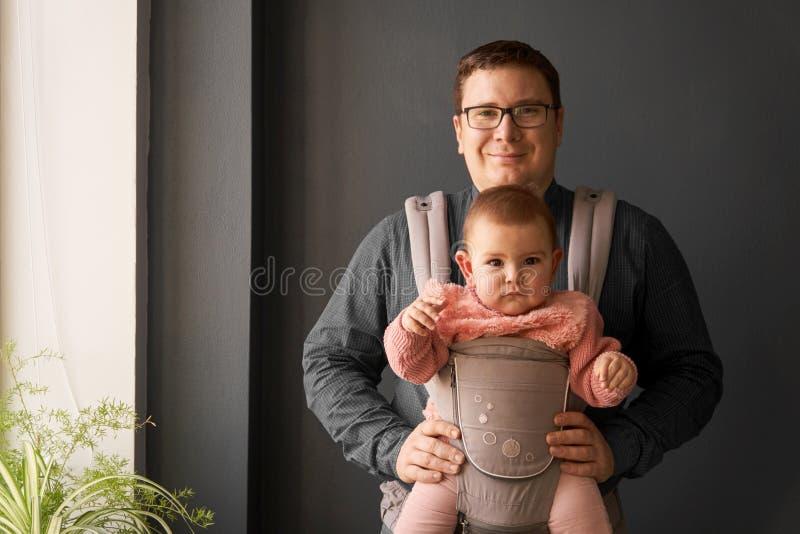Fathre e sua criança no portador de bebê na parede cinzenta do fundo, conceito vestindo do bebê fotos de stock