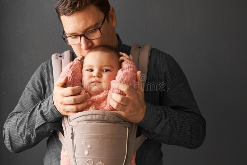Fathre e sua criança no portador de bebê na parede cinzenta do fundo, conceito vestindo do bebê foto de stock royalty free