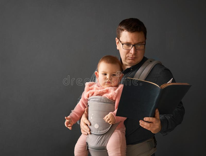 Fathre i jego dzieciak w dziecko przewoźniku przy popielatą tło ścianą, dziecko jest ubranym pojęcie obraz royalty free