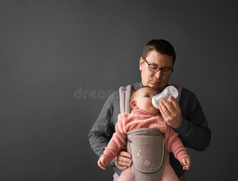 Fathre y su niño en el portador de bebé en la pared gris del fondo, concepto que lleva del bebé foto de archivo