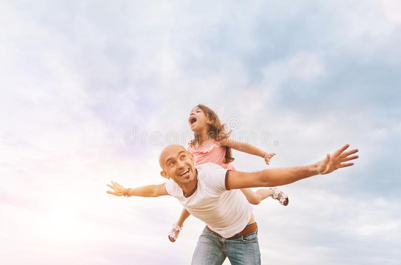 Fathrer e figlia sveglia che giocano come l'aeroplano immagine stock libera da diritti