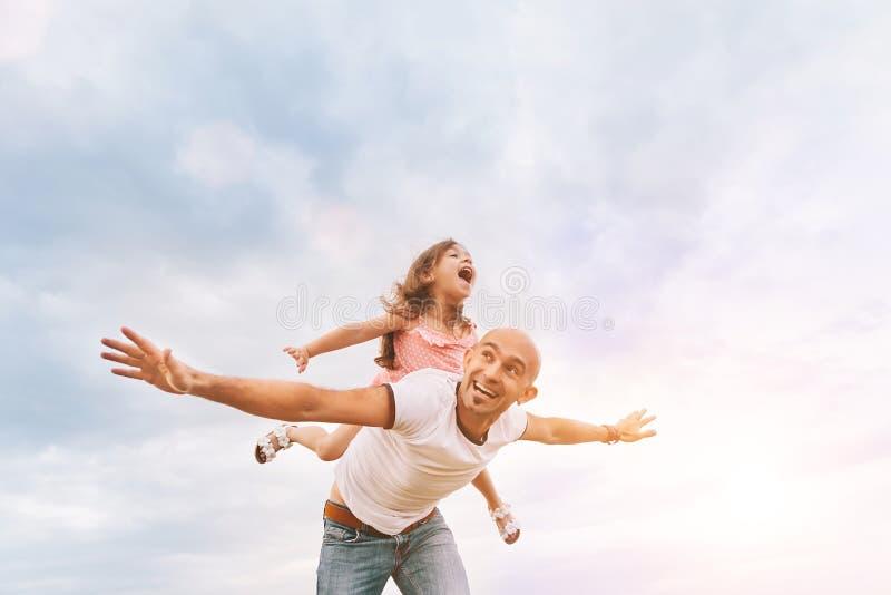 Fathrer en het leuke dochter spelen als vliegtuig stock foto's