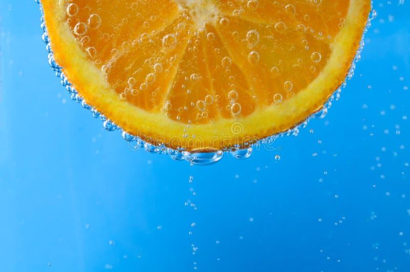 Fatia alaranjada fresca na água azul efervescente imagem de stock