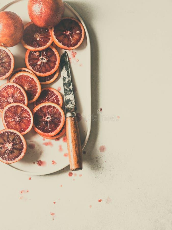 Fatia alaranjada vermelha do sangue cru na placa oval um fundo cinzento Fundo do citrino, vista superior Tonificando a fotografia fotos de stock royalty free