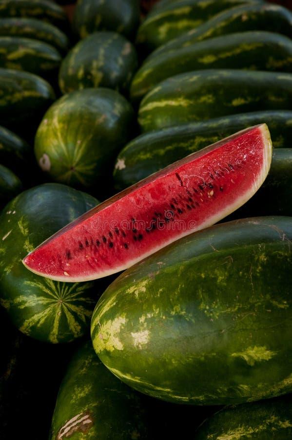 Fatia da melancia na cama de melancias inteiras imagem de stock