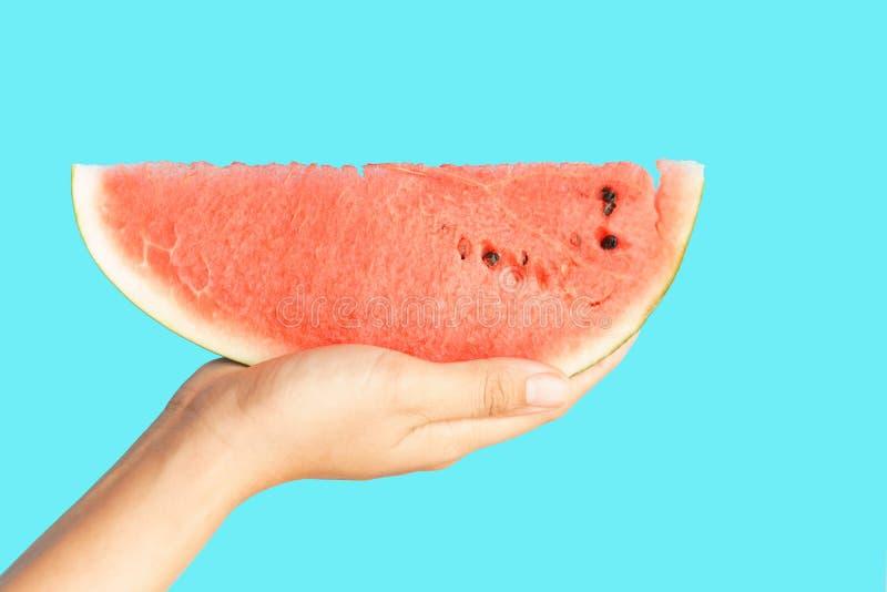 Fatia da melancia da terra arrendada da mão no conceito azul do fundo Fruto saudável da melancia para o alimento do verão e da di imagem de stock royalty free