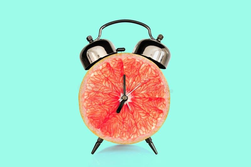 Fatia da toranja no despertador, fundo pastel azul o fruto e as vitaminas fazem dieta o conceito da nutri? fotografia de stock