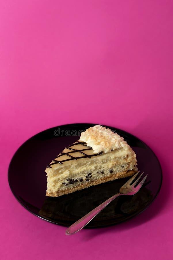 Fatia de bolo de camada com creme e pedaços de chocolate - fundo do rosa quente imagens de stock