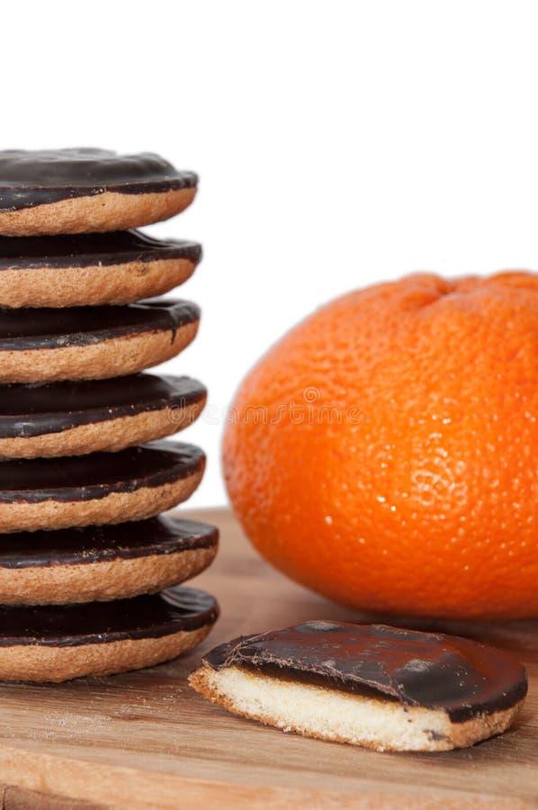 Fatia de bolo de jaffa com a pilha das cookies e da laranja imagem de stock