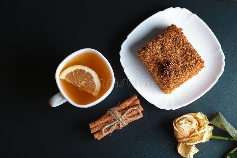 Fatia de bolo de mel mergulhado Medovik decorada com a estrela do anis na placa branca, varas da canela, um copo do chá com limão fotografia de stock royalty free