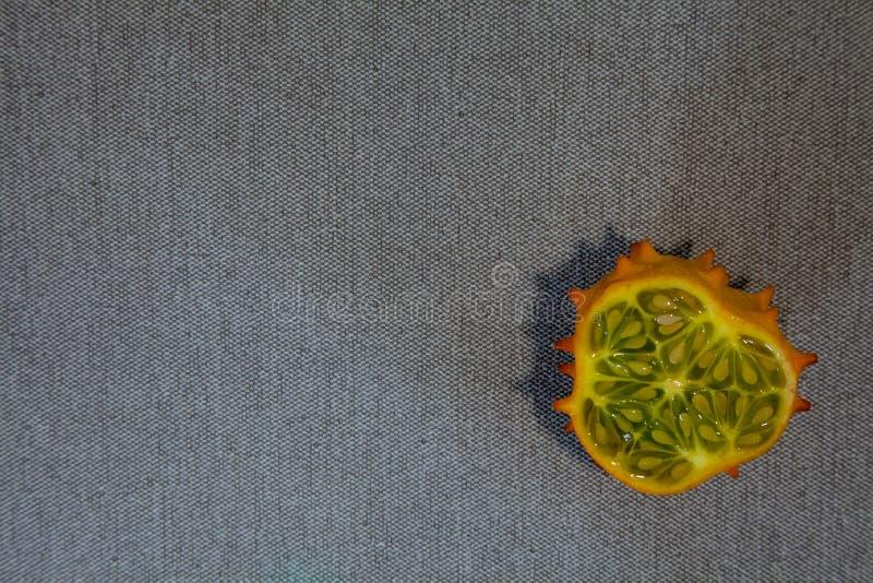 Fatia de Kiwano na matéria têxtil cinzenta foto de stock