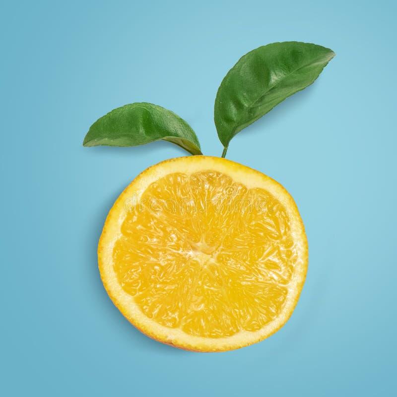 Fatia de laranja com as folhas no fundo azul Vista superior foto de stock royalty free