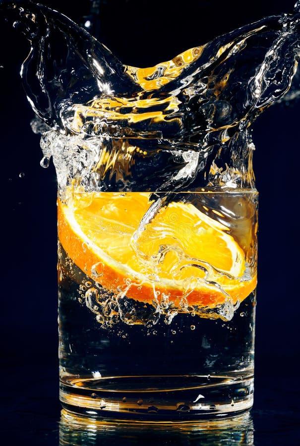 Fatia de laranja que cai para baixo no vidro com água imagem de stock royalty free