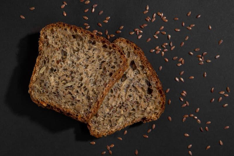 Fatia de multi fim saudável marrom do pão da grão acima no fundo preto foto de stock