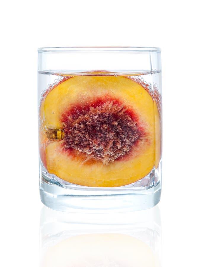 Fatia de pêssego no vidro da água imagem de stock royalty free
