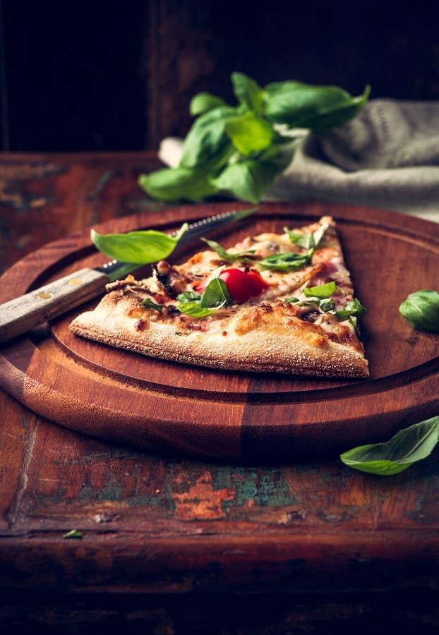 A fatia de pizza rústica cobriu com manjericão fresca imagens de stock