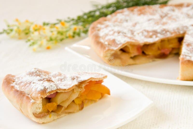 Fatia de torta com maçãs e os alperces secados imagem de stock