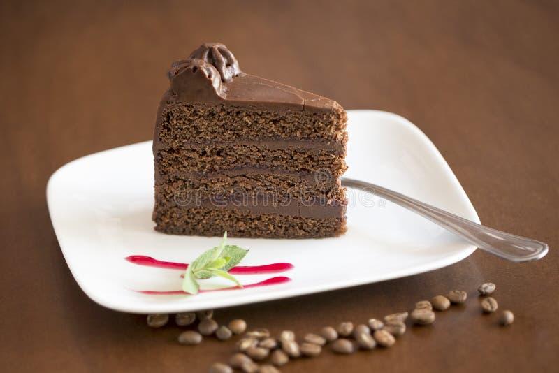 Fatia do bolo de chocolate com fundo marrom imagens de stock
