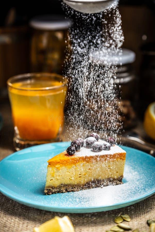 Fatia do bolo de queijo em uma placa azul Sugar Snow fotos de stock