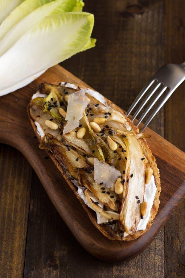 Fatia do pão com a chicória orgânica do assado, os pinhões e sésamo preto fotografia de stock
