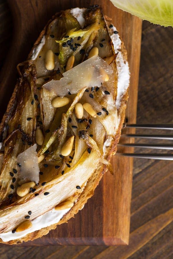 Fatia do pão com a chicória orgânica do assado, os pinhões e sésamo preto imagens de stock