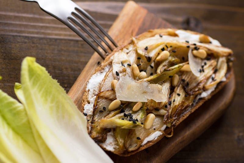 Fatia do pão com a chicória orgânica do assado, os pinhões e sésamo preto fotografia de stock royalty free